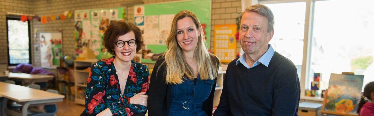 3 docenten naast elkaar in een klaslokaal
